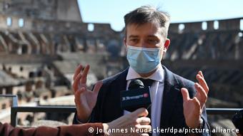 Pompeii's new director Gabriel Zuchtriegel speaks to journalists, wearing a mask