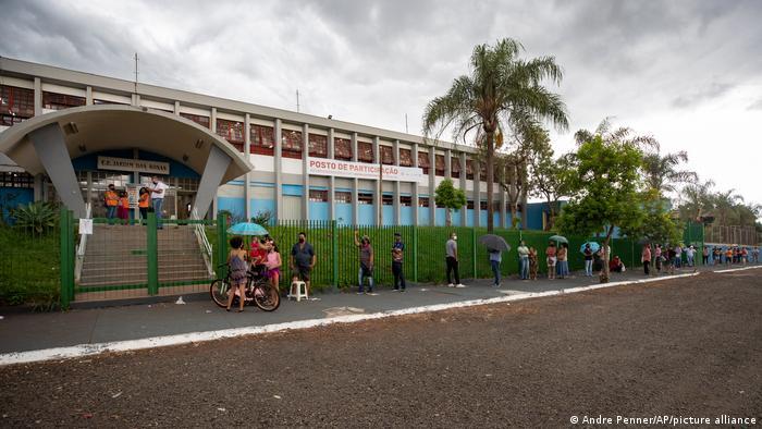 People wait in line outside a public school to get a shot of China's Sinovac CoronaVac vaccine in Serrana