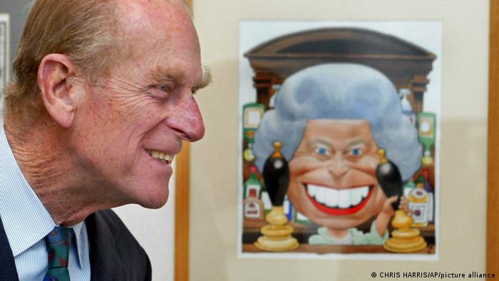 Prince Philip stands beside a cartoon of his wife Britain's Queen Elizabeth II behind the bar in the Old Vic pub from the TV show Eastenders