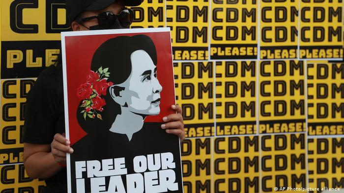 A protester in Myanmar holding a sign showing Aung San Suu Kyi that says Free our leader