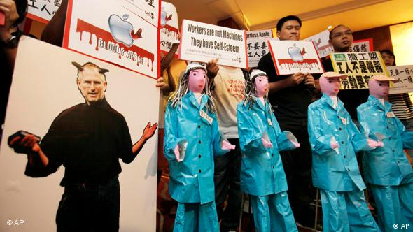 A cardboard cutout of Apple CEO Steve Jobs portrayed with devil's horns and paper figures symbolizing Chinese workers are placed by protesters outside a Foxconn's annual general meeting during a protest in Hong Kong Tuesday, June 8, 2010.