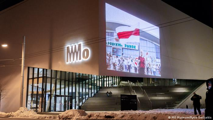 This image shows a photograph being projected on the museum walls. The photograph shows an eldery woman in a red pullover holding a big flag.