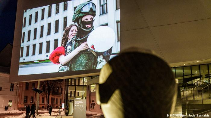 This picture shows a photograph projected on the outer walls of the MO museum in Vilnius. The photograph depicts a woman protester hugging a soldier in uniform. The museum is closed because of the COVID-related lockdown.