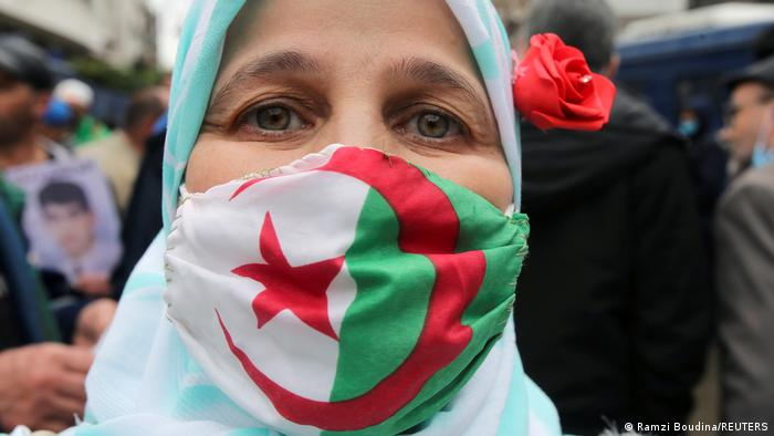A woman wearing a protective face mask with the Algerian flag takes part in a protest to mark the second anniversary of a mass protest movement demanding political change, in Algiers, Algeria February 22, 2021.