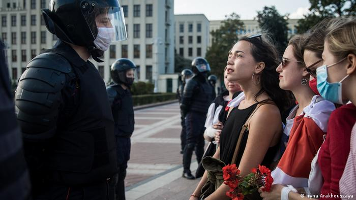 A picture from the exhibition, The Future of Belarus, Fueled by Women. Many young women face policemen from the special unit of the Belarusian police. The women are wearing dresses, make-up and lipstick, and are carrying flowers.