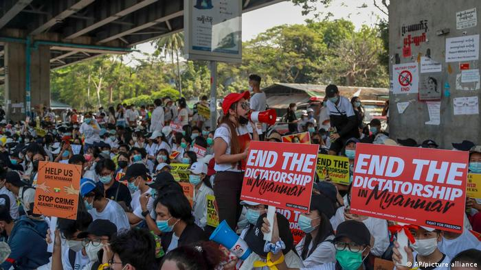 Protesters hold signs reading 'end the dictatorship' as they gather in Yangon
