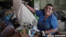 A woman empties a bag of garbage in Costa Rica