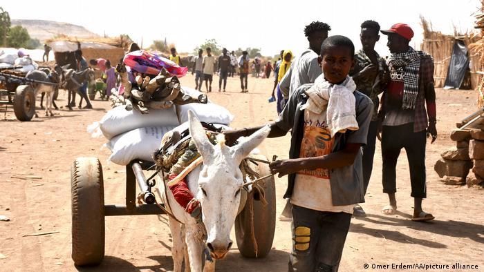 Un niño etíope que huyó de Tigray lleva alimentos de una ONG