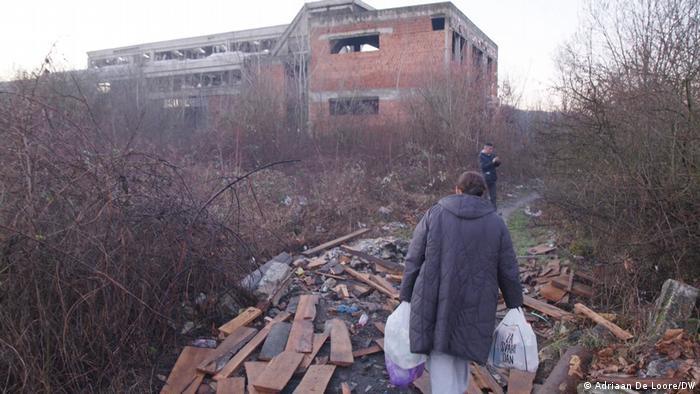 Ruševina, ispred nje dvije osobe, jedna novi pune vrećice