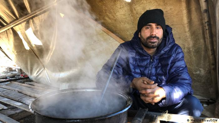 Migrante sentado atrás de panela fumegante numa barraca