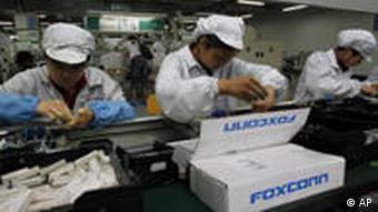 Foxconn Arbeiter in weißer Arbeitskleidung am Fließband Foto:AP)