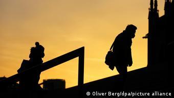 Люди в масках идут на рассвете вверх по лестнице