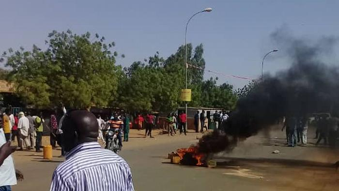 Protesters watch as a tire burns on a street.
