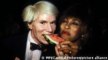 Енді Воргол зі скибкою кавуна в роті та Тіна Тернер, яка теж тримається за скибку, фото 1981 року