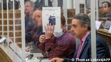 Die beiden Angeklagten im Gerichtssaal in Koblenz zwischen ihren Übersetzern. Ein Angeklagter verdeckt sein Gesicht mit einem Blatt Papier.
