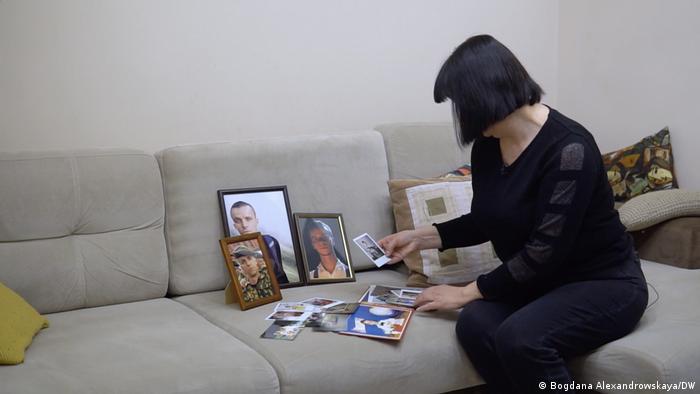 Мать погибшего Романа Бондаренко смотрит фотографии сына