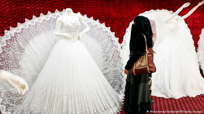 A veiled woman looking at a bridal gown