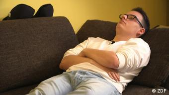 Уставший подросток лежит на диване