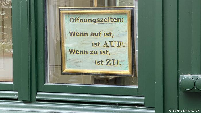 Sign on closed restaurant door in Monschau, Germany, reading .'When we're open, we're open. When we're closed, we're closed.'