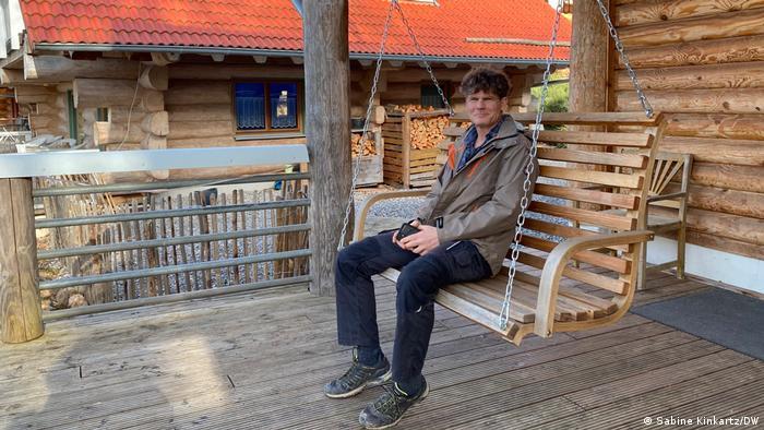 Jan Lehmann sitting in a wooden swing on a porch