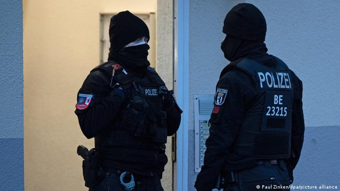 Two police officers stand outside a building in Moabit