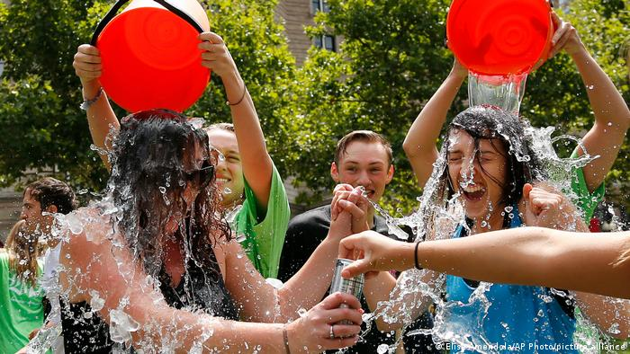 Young people dump buckets of ice water on each other