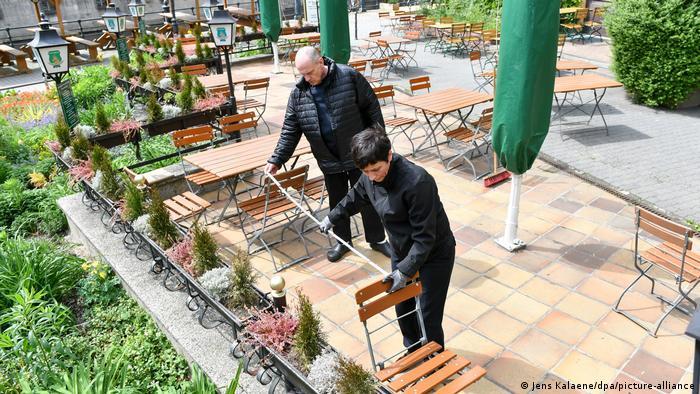 People measuring the distance between chairs on a Biergarten terrace