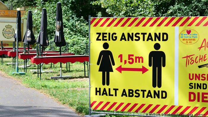 large yellow sign, pictogram of two people keeping their distance