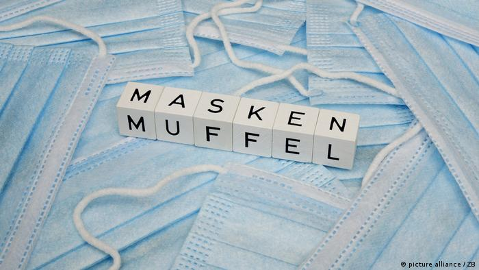 blue surgical face masks and white block that read: Maskenmuffel