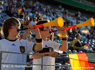German soccer fans blowing vuvuzelas with the German national colors