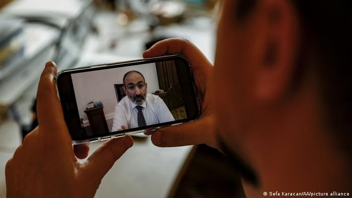 A person holds a mobile phone screen showing Prime Minister of Armenia, Nikol Pashinyan speaking during a live broadcast over Facebook after the Armenian military called for the resignation of Prime Minister Nikol Pashinyan in Moscow, Russia on February 25, 2021.