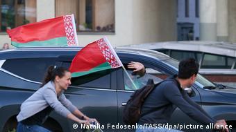 Парень и девушка на велосипедах и белорусские флаги на проезжающей машине