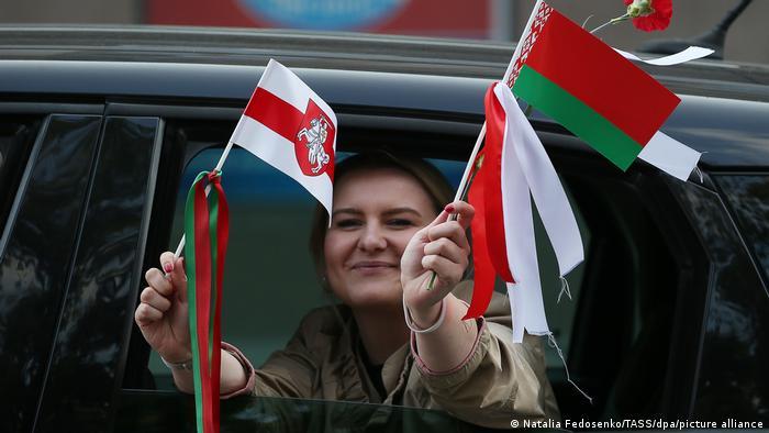 Женщина держит в руках официальный и исторических белорусские флажки