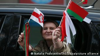 Девушка в окне машины держит в руках два белорусских флага: официальный и бело-красно-белый