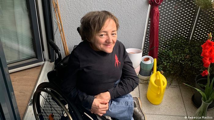 Rebecca Maskos sitzt im Rollstuhl auf einem Balkon und schaut in die Kamera
