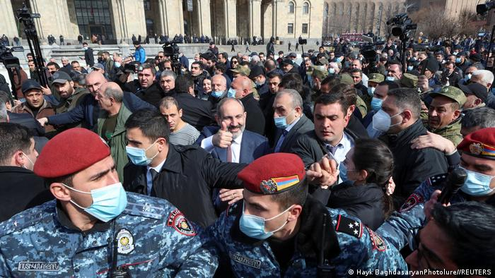 Armenian Prime Minister Nikol Pashinyan greets supporters while military personal keep crowds away