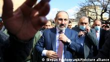 Armenian Prime Minister Nikol Pashinyan fixes his tie ahead of a rally in Yerevan