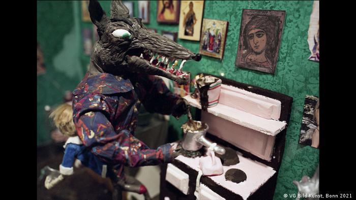 Eine sexuell erregte Wolfsfigur, die Kaffee kocht im Film von Natalie Djurberg & Hans Berg. Das Filmstill hängt in der Ausstellung Wild/Schön in der Kunsthalle Emden.