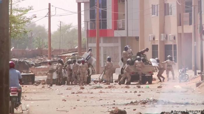 Eine Gruppe von Bereitschaftspolizisten mit Schutzausrüstung steht vor zwei Pickup-Fahrzeugen in einer Straße von Nigers Haupstadt Niamey, auf dem Boden liegen Steine (24.02.2021)