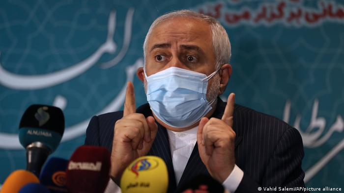 Javad Zarif speaks while wearing a surgical mask
