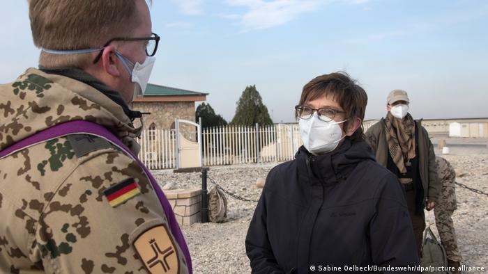 Annegret Kramp-Karrenbauer speaks with a soldier