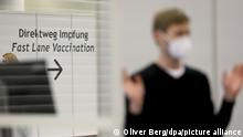 A worker at a vaccination center in Cologne next to a sign that reads Fast Lane Vaccination