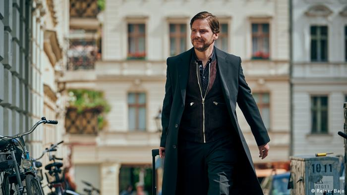 Film still from 'Next Door': Daniel Brühl walking in a Berlin street