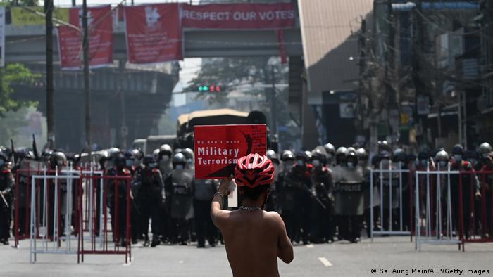 Ein einzelner Mann mit einem Protestschild steht auf einer Straße in Yangon, Myanmar, bewaffneten Sicherheitskräften gegenüber