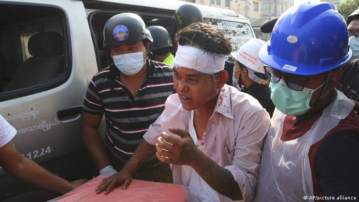 Ein verwundeter Demonstrant wird in Mandalay von Helfern versorgt