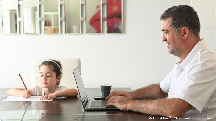 A man works at home on a laptop as his young daughter works on homework at his side