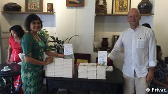 Jan-Philipp Sendke and his publisher in Myanmar standing at a table and holding books.