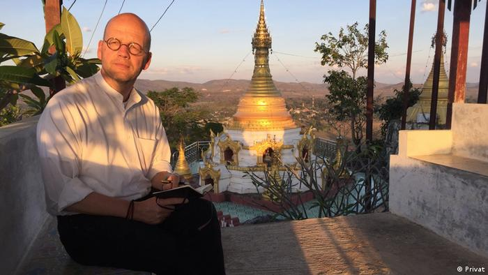 Jan-Philipp Sendke sitting outside with a notebook in his hand and near a pagoda in Myanmar.
