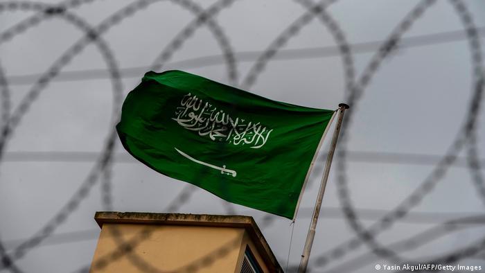 A Saudi Arabia flag flies behind barbed wires