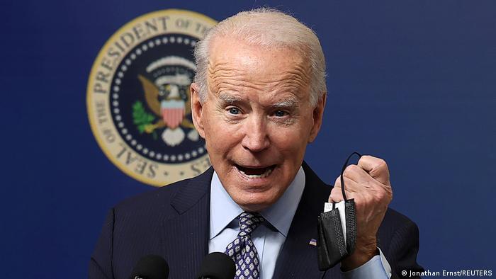 Joe Biden com máscara na mão